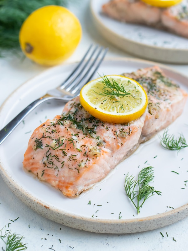 Salmon is served on a a white plate with a fork.