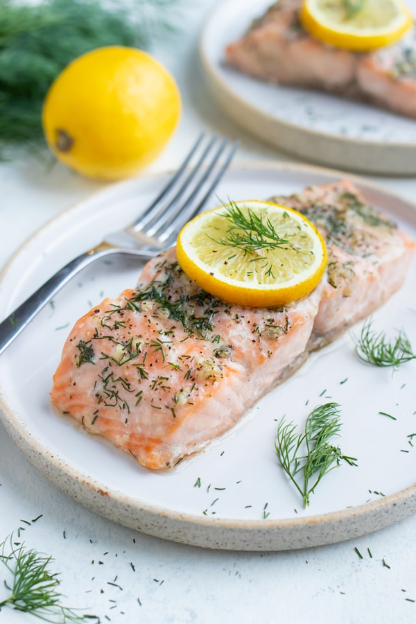 Fresh dill is placed on a plate with a healthy salmon dish.