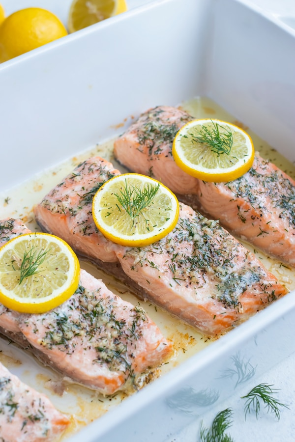 20-minute baked salmon recipe is shown in a white baking dish on the counter.