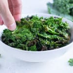 A hand is shown lifting out a crunchy kale chip from a bowl.