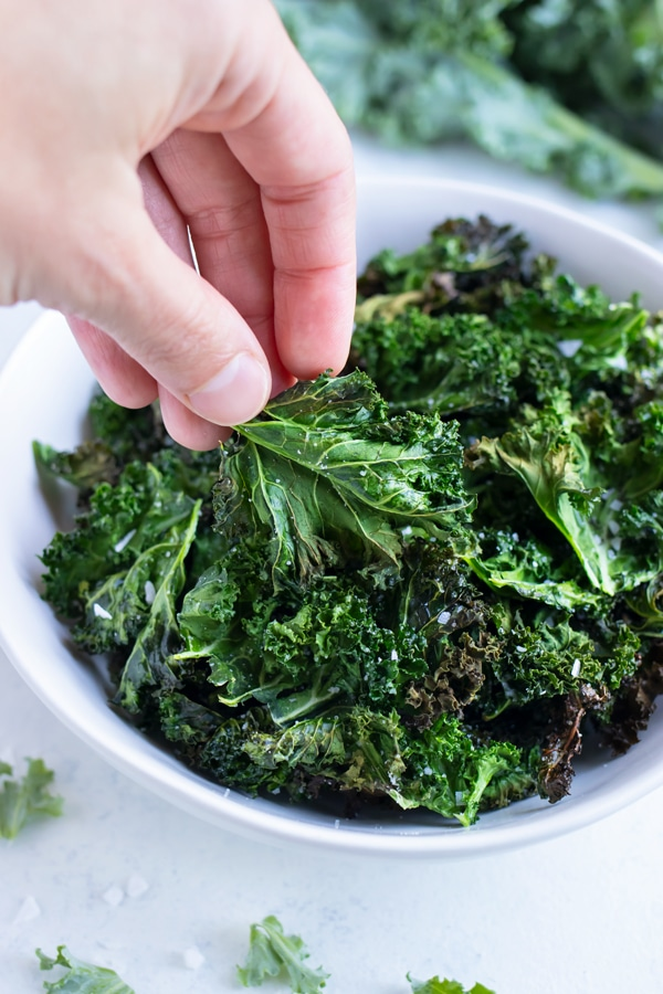 A hand lifts up a crunchy homemade kale chip from the bowl.