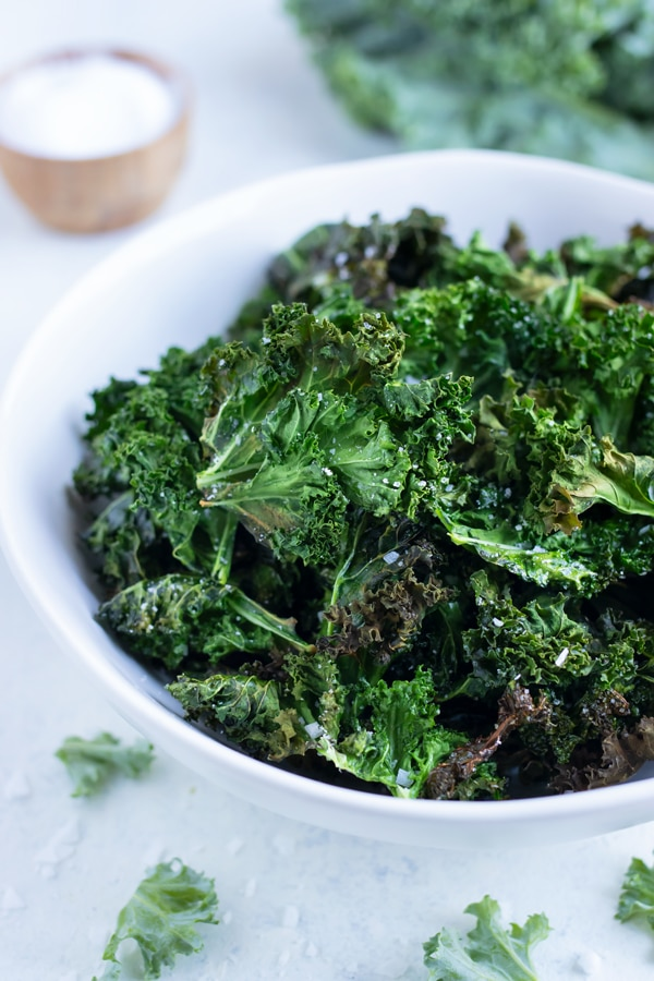 Homemade kale chips are served in a white bowl on the counter.