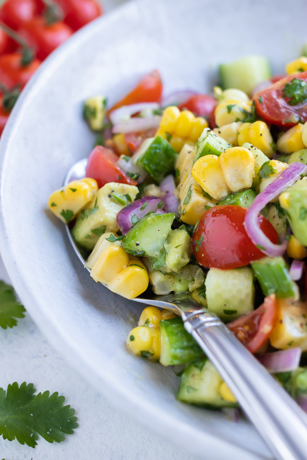 Avocado corn salad is served from a bowl for a light and refreshing side.