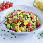 Avocado corn salad is served from a white bowl for a healthy picnic side dish.