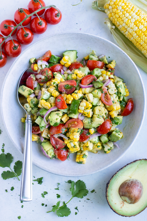 A bowl of avocado corn salad is set on the counter with tomatoes, avocado, and corn on the cob.