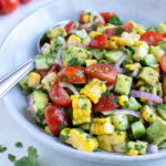 Avocado corn salad is served with a metal spoon from a white bowl.