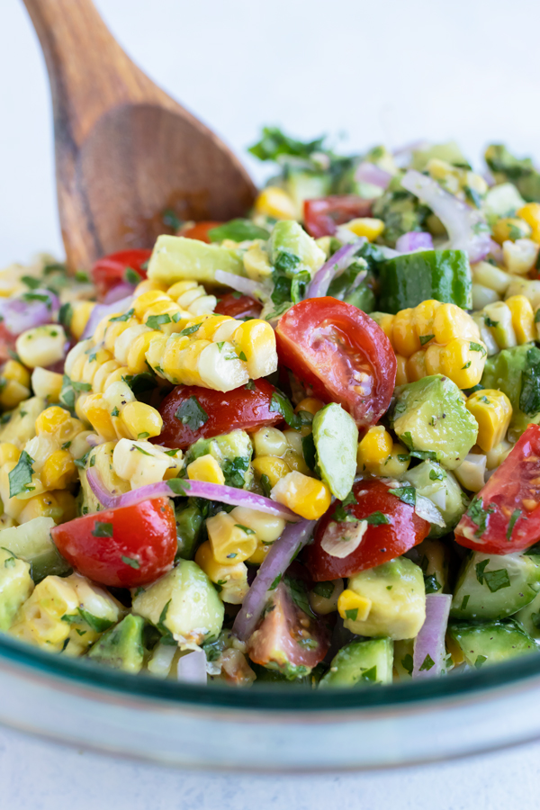 Avocado corn salad is dished from a glass bowl for a picnic or BBQ side dish.