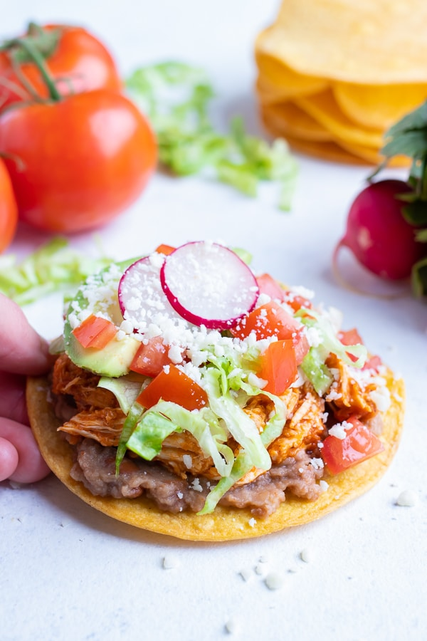 Cotija cheese is added to the top of the chicken tostada.