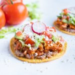 Two chicken tinga tostadas are shown on the counter.