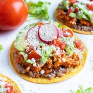 Easy chicken tinga tostadas are shown on the counter.