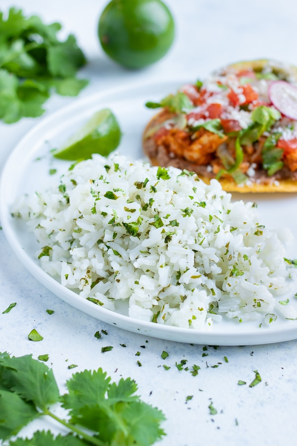 A side of cilantro lime rice is served with tacos on a plate.