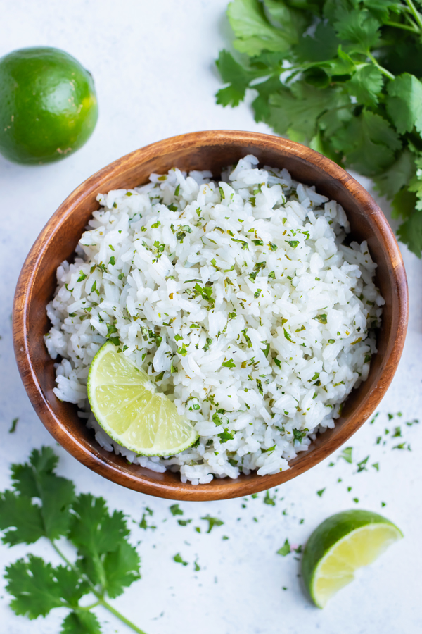 Cilantro Rice is served from a wooden bowl with fresh limes and cilantro.