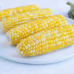 Four ears of corn are served on a plate for a side dish.