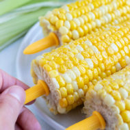 A hand is shown holding onto the plastic corn cob holders.