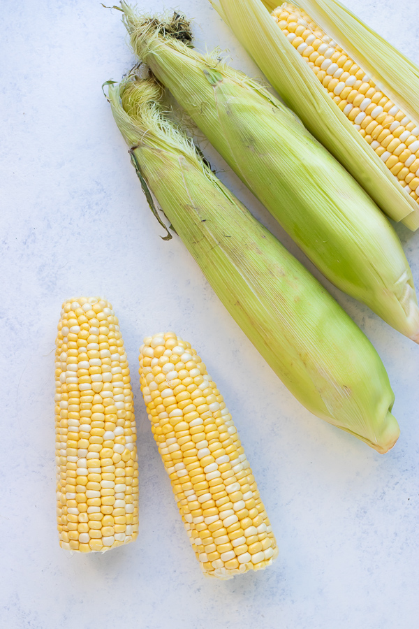 Corn with and without husks are shown on the counter.