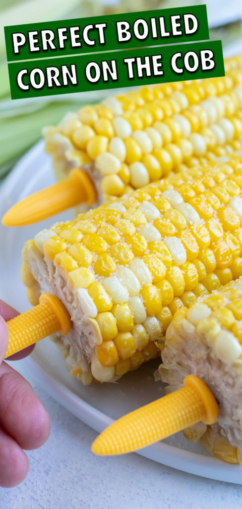 Yellow plastic corn cob holders are used to help hold the corn.