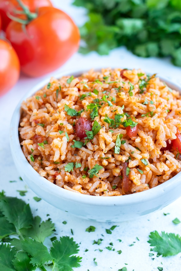 Pressure cooker Mexican rice is topped with fresh cilantro and served from a bowl.