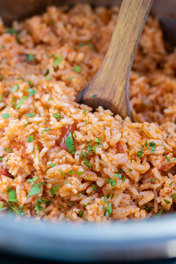 A wooden spoon serves the Mexican rice from the instant pot.