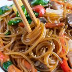 Glass noodles in a Japchae recipe are twirled by chopsticks.