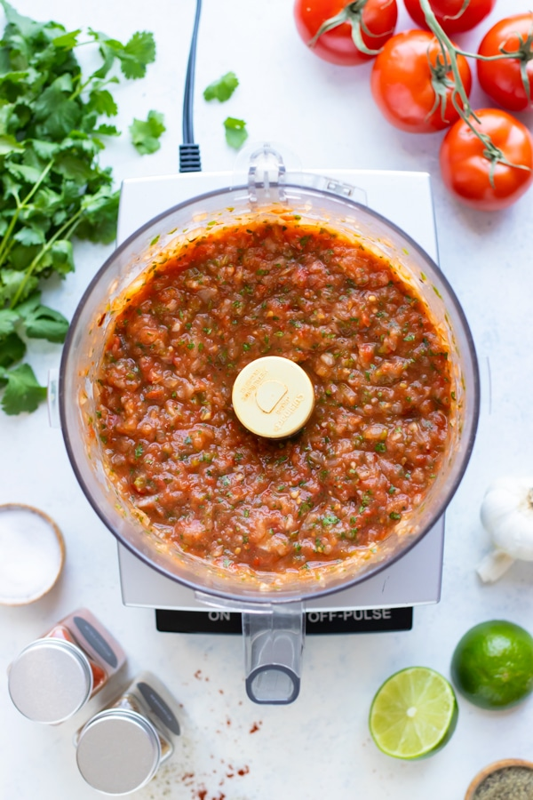 Salsa ingredients are pulsed in a food processor.