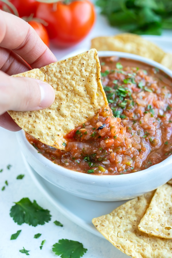 A tortilla chip is dipped into the bowl of roasted tomato salsa.