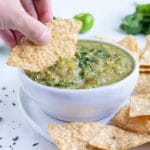 A chip is dipped into a white bowl filled with tomatillo salsa.