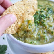 A chip is dipped into a big bowl of homemade salsa verde.