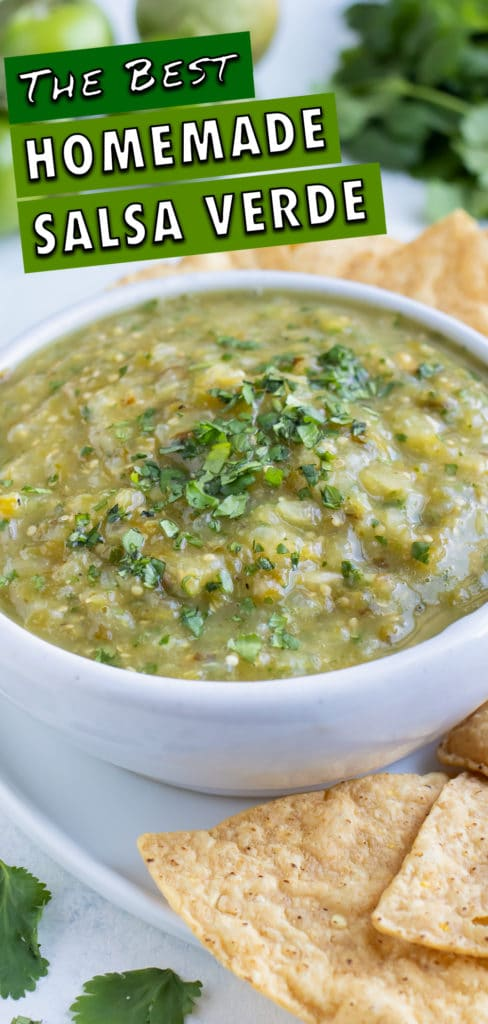 A bowl of salsa verde is served with a plate of chips.