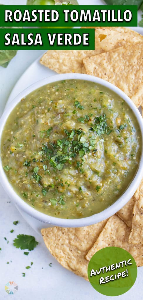 A bowl of tomatillo salsa verde is placed beside tortilla chips.