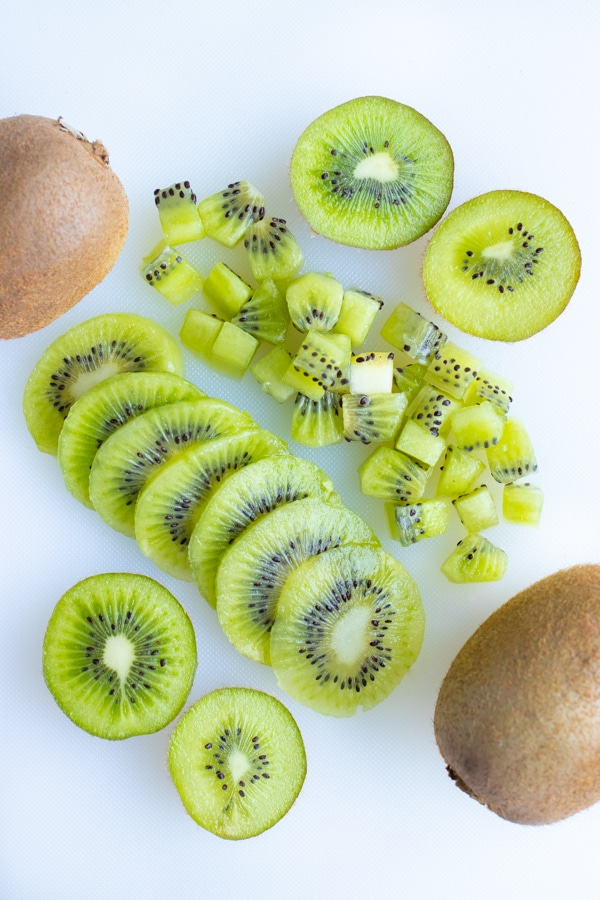 Kiwi is sliced, dices, and left in half pieces.