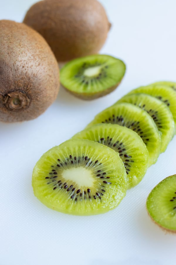 The kiwi slices are set on the counter next to whole kiwis.