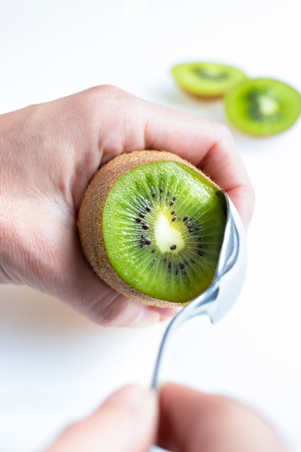 A kiwi is being cut and peeled by using the spoon method.