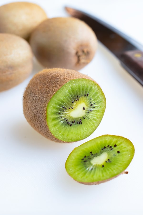 A kiwi with the end cut off is set on the counter next to a knife.