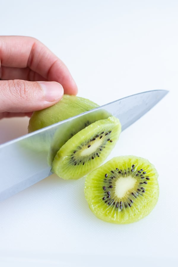 A knife is used to create slices of kiwi.