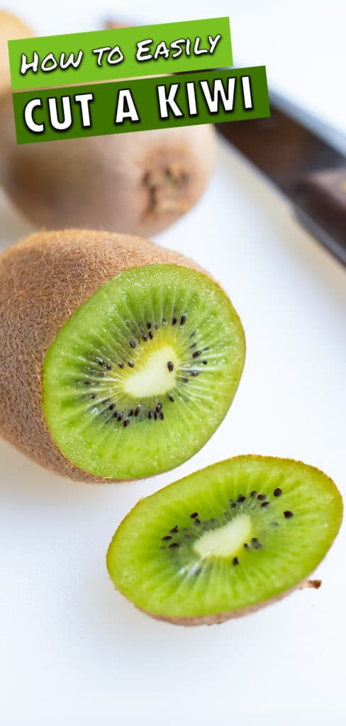 A long knife is used to cut off the end of one kiwi.
