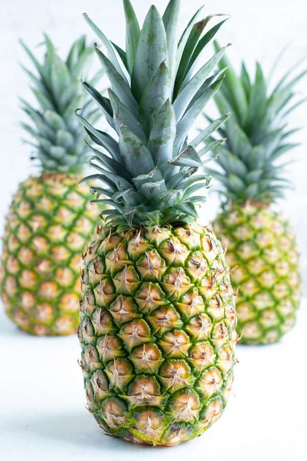Three whole pineapples are set on the counter.