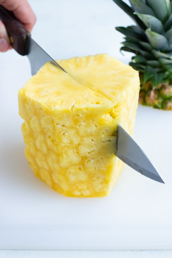 The whole pineapple is cut in half with a knife.