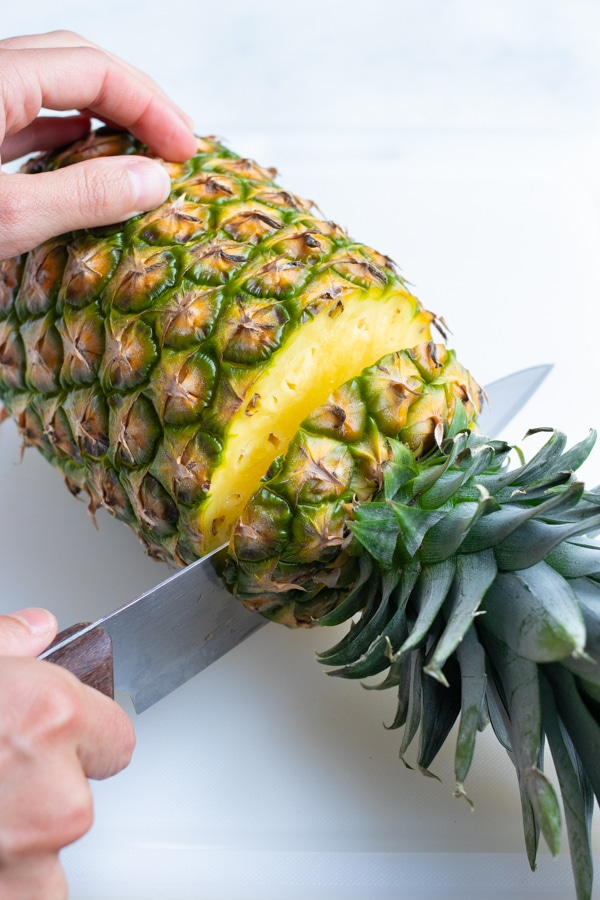 The top of the pineapple is cut off with a large knife.