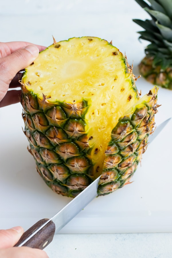 The rough pineapple skin is removed with a knife.