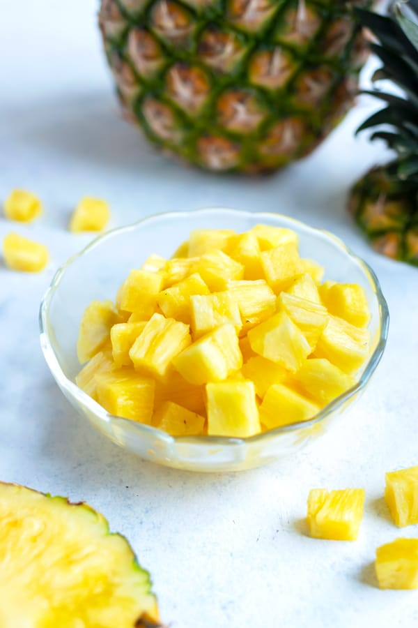 A bowl of pineapple cubes is shown on the counter.