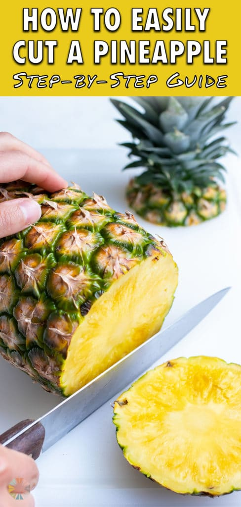 The bottom end of the pineapple is cut off with a large knife.