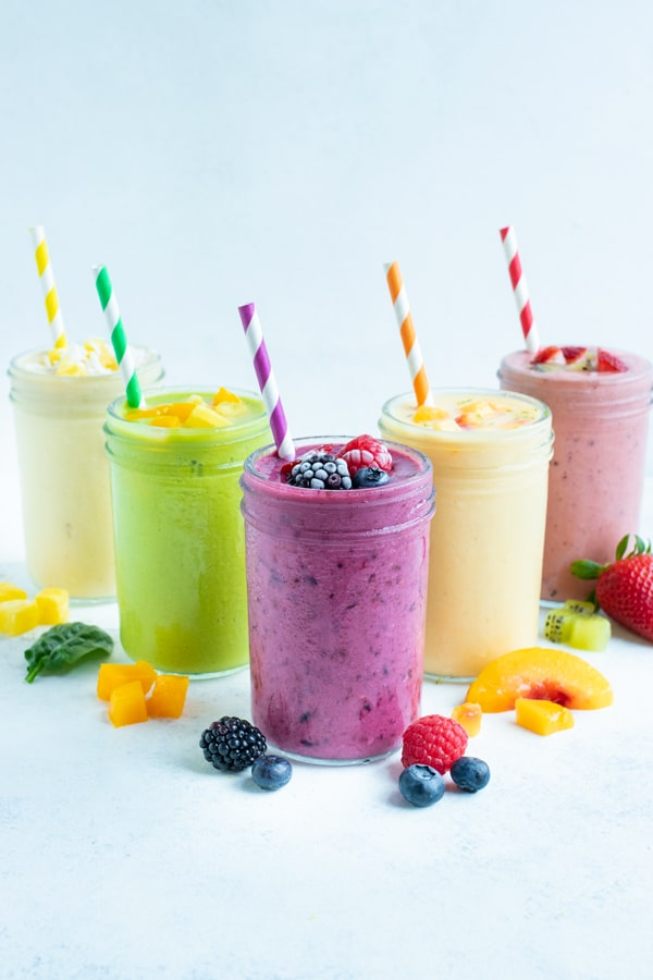 5 different types of frozen fruit smoothie recipes are set on the counter.
