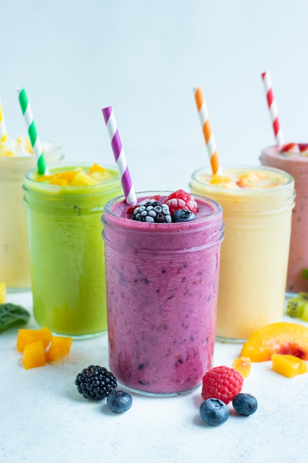 Fruit smoothies are set on the counter and enjoyed for a delicious breakfast drink.