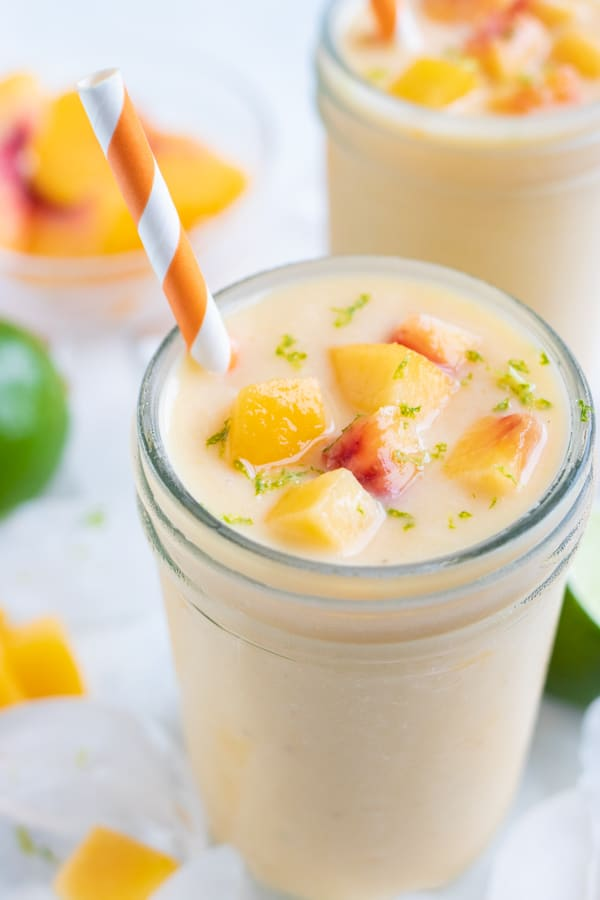Frozen peach smoothie is set on the counter before enjoying.