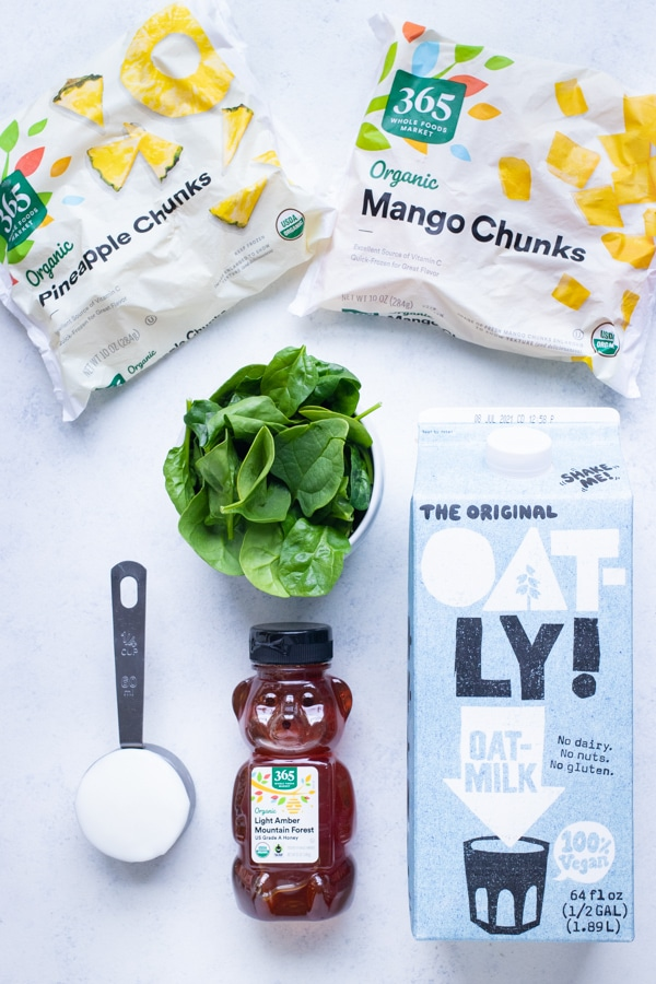 Spinach, oat milk, honey, frozen mango, frozen pineapple, and yogurt are the ingredients in this recipe.