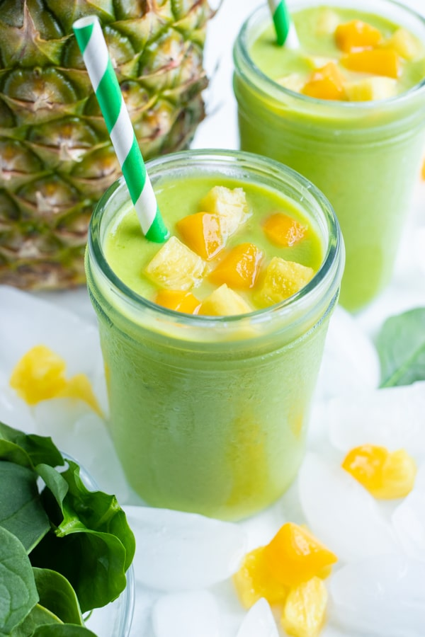 Two healthy green smoothies is set on the counter in a glass with a straw.