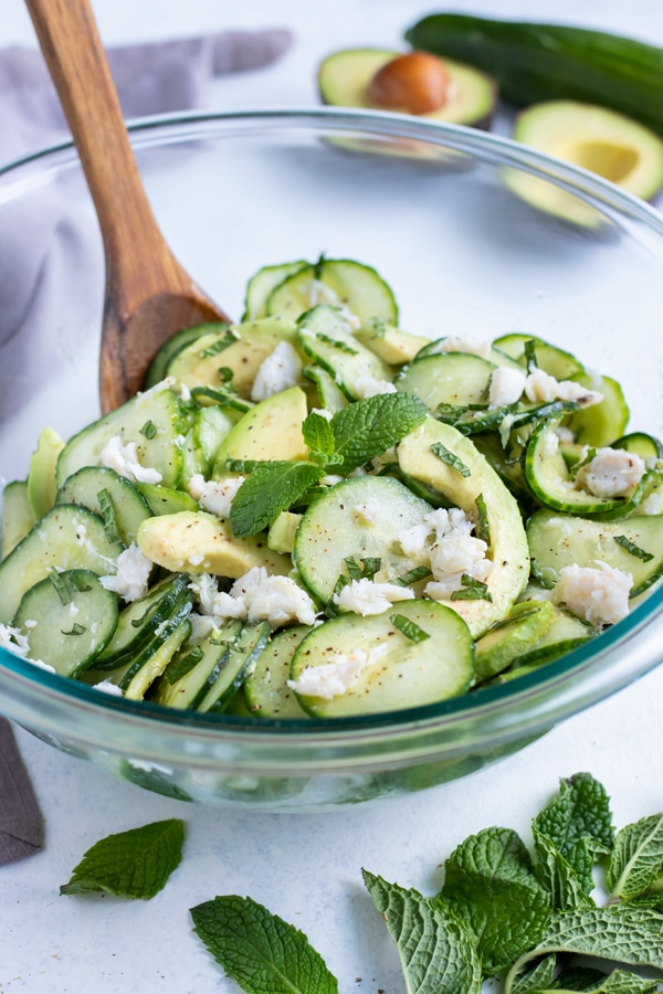 Cucumber crab salad is made in a glass bowl for a low-carb recipe.