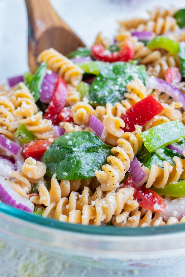 A glass bowl of Italian dressing pasta salad is served from a glass bowl with a wooden spoon.