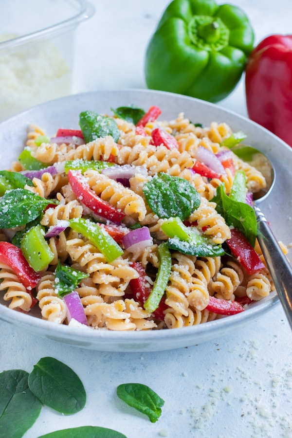 A bowl of Italian Pasta Salad is served with a spoon for a picnic side dish.