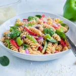 A white bowl is filled with Italian pasta salad.
